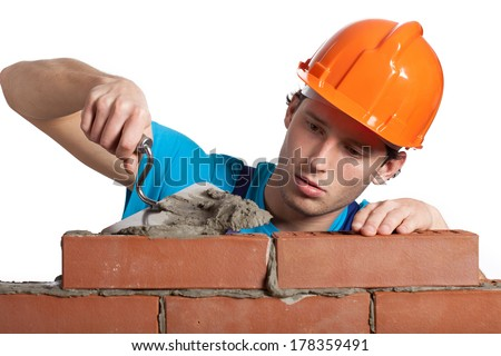 A bricklayer putting bricks being very concentrated - stock photo