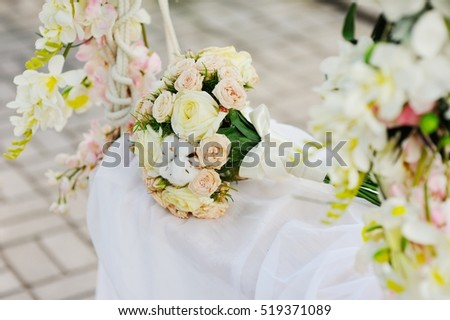 a bridal bouquet of flowers on a swing. wedding decorations