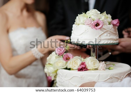 A bride and a groom is cutting their wedding cake - stock photo