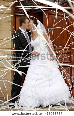 A bride and groom behind paper confetti