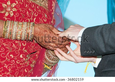 A bride and groom exchange rings during a wedding ceremony - stock photo