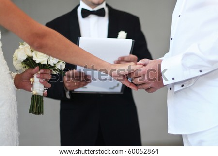 A bride and groom hold hands as a priest performs a wedding ceremony