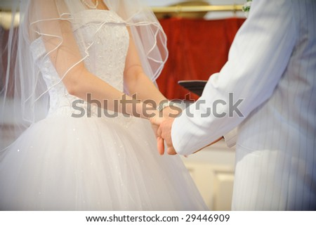 A bride and groom holding hands at ceremony - stock photo