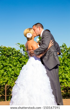 A bride and groom seal the deal with a kiss during their wedding day ceremony at a vineyard winery in Oregon. - stock photo