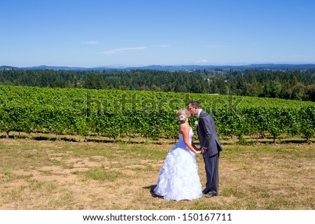 A bride and groom share a kiss after their ceremony on their wedding day at a vineyard winery in Oregon outdoors. - stock photo