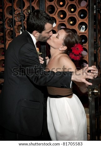 A bride and groom share a kiss in a wine cellar after their wedding.