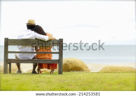 A bride and groom sitting wooden bench on the beach - stock photo