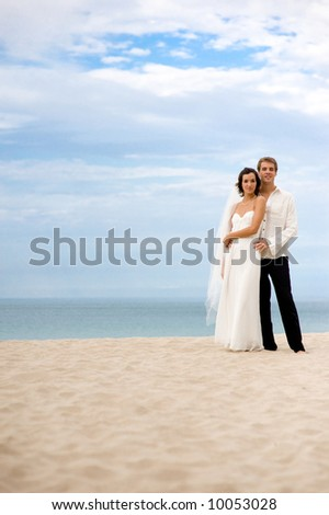 A bride and groom standing on beach