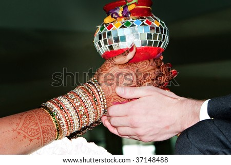 A bride and groom take part in a Hindu wedding ceremony - stock photo