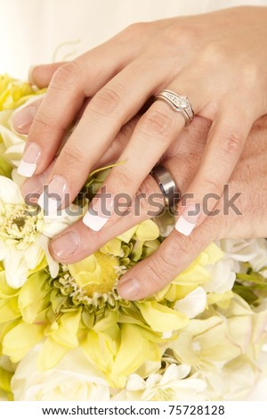A bride and groom with their hands on top of the flowers, showing off their rings.