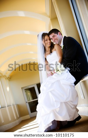 a bride and her groom, she is sitting in his lap and he is looking at the camera. A very sweet and attractive couple. - stock photo