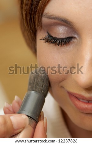 A bride getting her makeup done - stock photo