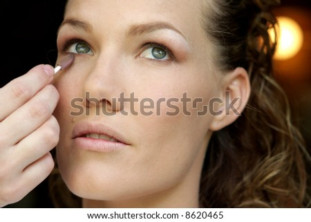 A bride having her makeup done on her wedding day - stock photo