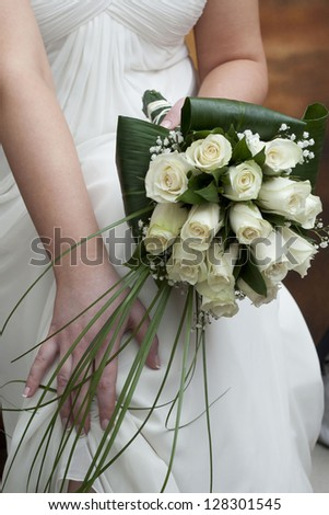 A bride holds her bouquet of white roses - stock photo