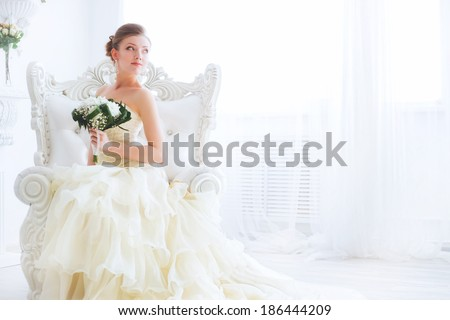 A bride in a beautiful dress holding a bouquet of flowers and greenery. Wedding. wedding bouquet. Bride's morning. Fine art wedding. Happy Bride waiting groom. - stock photo