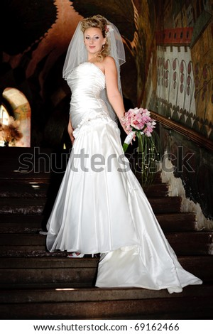 a bride in a gown with a long train on the stairs - stock photo
