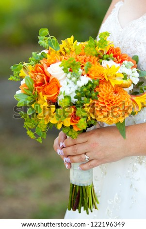 A bride in her white wedding dress holds her bouquet of orange, green, and yellow flowers on her wedding day.