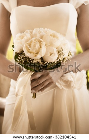 a bride is holding a bouquet