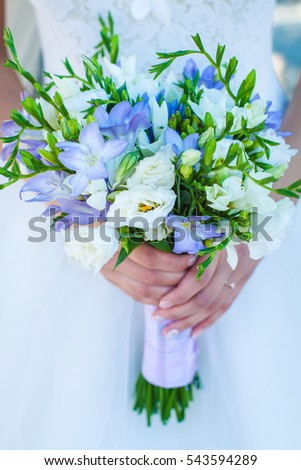 a bride keeps bouquet with 	