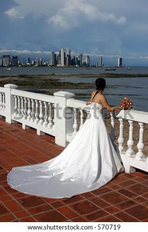 A bride looking towards the sea. - stock photo