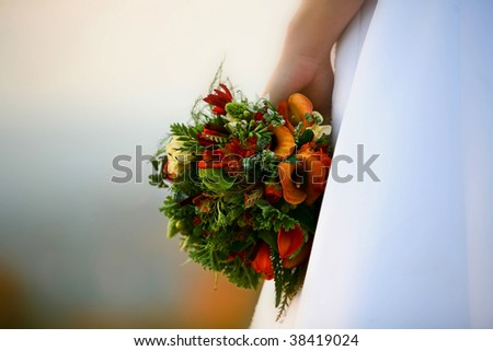 A bride's hand holding a beautiful bouquet - stock photo