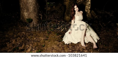 A bride sitting beneath a tree in dark woods - stock photo
