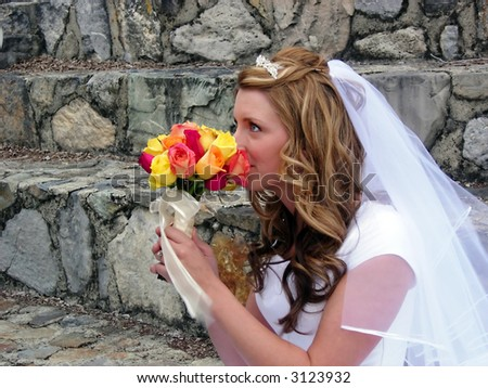 A bride smelling her bouquet - stock photo