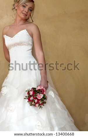 A bride standing against a wall - stock photo