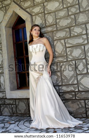 A bride standing against a wall in her dress - stock photo