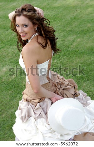 A bride standing on grass holding a hat