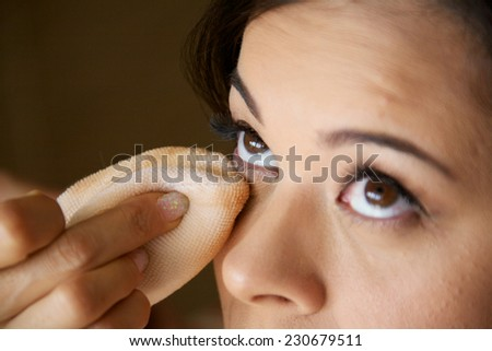 A bride to be getting ready for the wedding and getting makeup applied - stock photo
