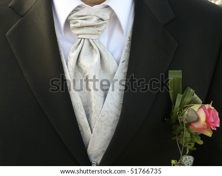 A bridegroom with a nice grey silk tie and a flower decoration on his black tuxedo