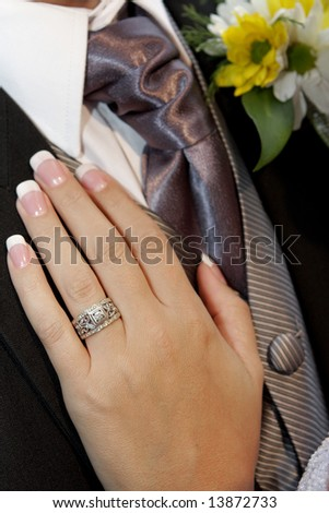 A brides hand on grooms chest - stock photo