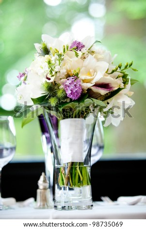 A brides wedding bouquet of flowers sitting in a vase full of water. Very shallow depth of field, focus on the purple flowers - stock photo