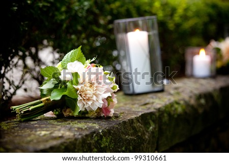 a brides wedding bouquet of flowers sitting on a wall - stock photo