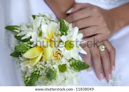 A brides wedding bouquet on her lap - stock photo