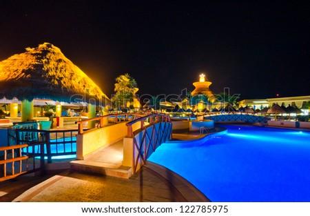 A bridge across swimming pool in a luxury caribbean resort at night, dawn time. Bahia Principe, Riviera Maya, Mexican Resort. - stock photo