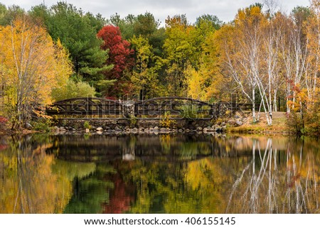 A Bridge and Colorful Trees Reflected in a Pond in Fall - stock photo