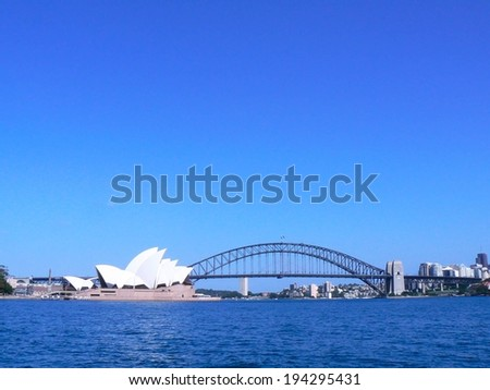 A bridge and opera house across the Sydney harbor. - stock photo