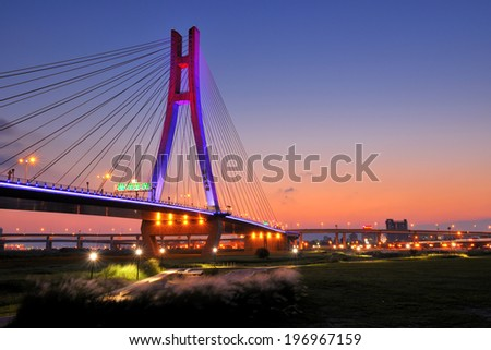 A bridge and the lights of a city at sunset.