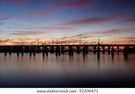 a bridge crossing a river before sunrise - stock photo