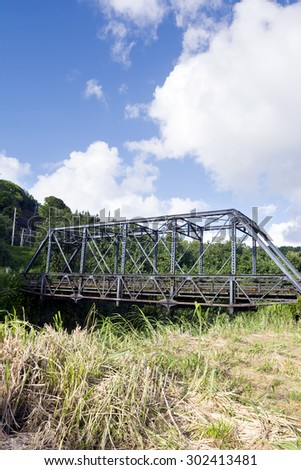 A bridge in Kauai, Hawaii allows drivers to cross a river fed by local waterfalls and frequent rain. - stock photo
