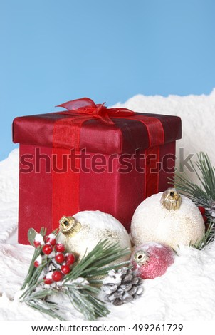A bright and cheerful Christmas scene full of snowy baubles and pines with a red gift box.