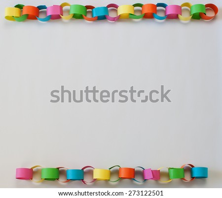 A bright and colorful paper chain border on a white background - stock photo