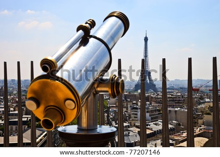 A bright and shiny telescope on the Arc de Triomphe in Paris with the Eiffel Tower in the background. - stock photo