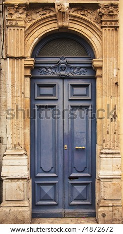 A bright blue door in an old building with ornate stonework on a street in France - stock photo
