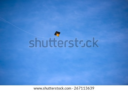 A bright colored kite soaring against the blue sky - stock photo
