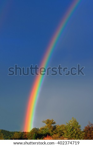 A bright, colorful rainbow is visible across the deep blue sky. The colors of the rainbow are red, yellow, green and blue. At the bottom of the image, there are a couple of trees. - stock photo