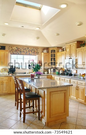 a bright modern kitchen with wooden furniture and a roof window - stock photo