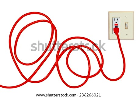 A bright orange extension cord plugged into an electrical outlet. - stock photo